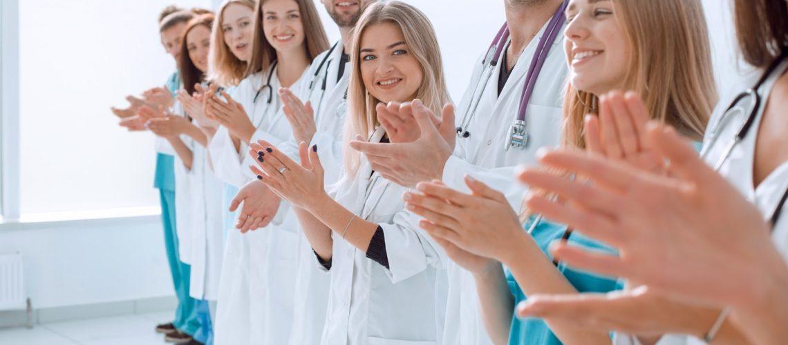 top view. a group of smiling doctors pointing at you. photo with copy space